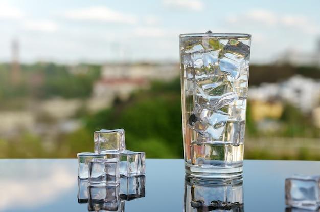 Świeży zimnej wody szkło z kostkami lodu na krajobrazie