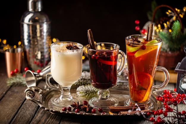 Świeży żółty grog ajerkoniakowy i owocowe czerwone grzane wino z wyborem dekoracji świątecznych