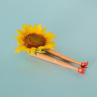Świeży żółty słonecznik i nogi lalki na niebieskim tle pastelowych. lato ogrodnictwo tropikalna dżungla sztuka abstrakcyjna