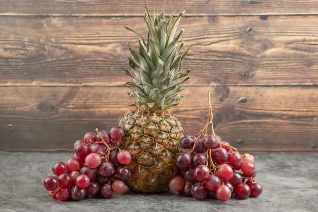 Świeżych czerwonych winogron z dojrzałym ananasem na marmurowej powierzchni.