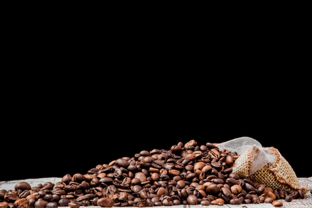 Świeżych palonych ziaren kawy wypadających z worek na czarnym tle. brązowe ziarna kawy rozsypane z torby na stole