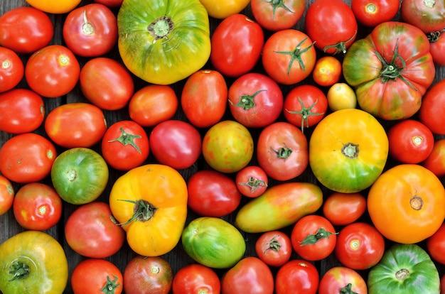 Świeżych pomidorów gospodarskich na drewnianym tle różnym stopniu dojrzałości