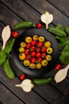 Świeżych warzyw dojrzali ogórki czerwoni i żółci pomidory i rzodkwie na drewnianym