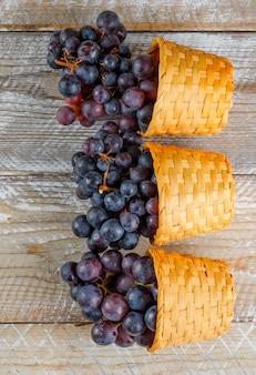 Świeżych winogron w wiklinowych koszach na drewnianym tle. widok z góry.