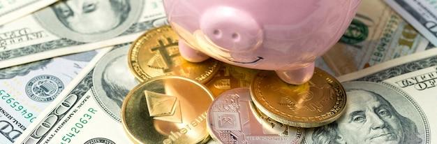 Świnia skarbonka na tle banknotów 100 usd i fizycznych monet bitcoinów