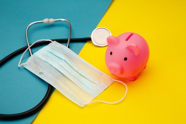 Świnka skarbonka, maska na twarz i stetoskop na kolorowe. wydawanie pieniędzy na pigułki i kosztowność koncepcji medycyny.