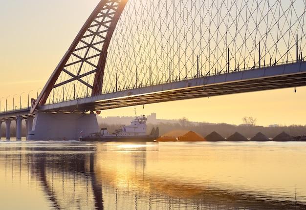 Świt bugrinsky bridge nowoczesny łukowy most drogowy nad rzeką ob w złoty poranek