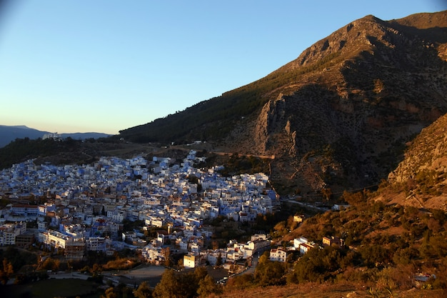 Świt nad miastem chefchaouen maroko. promienie słoneczne oświetlają zbocza gór i dachy domów. niebieskie miasto