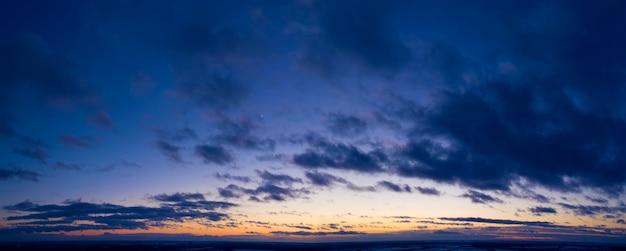 Świt ponad chmurami, fioletowe światło słoneczne oświetla poranne niebo.