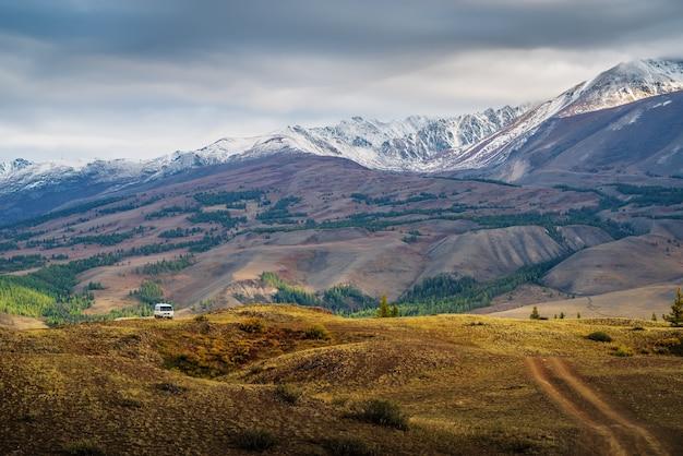 Świt w dolinie chuy, turystyczny minibus na polnej drodze na zboczu wzgórza. rosja, góra ałtaj