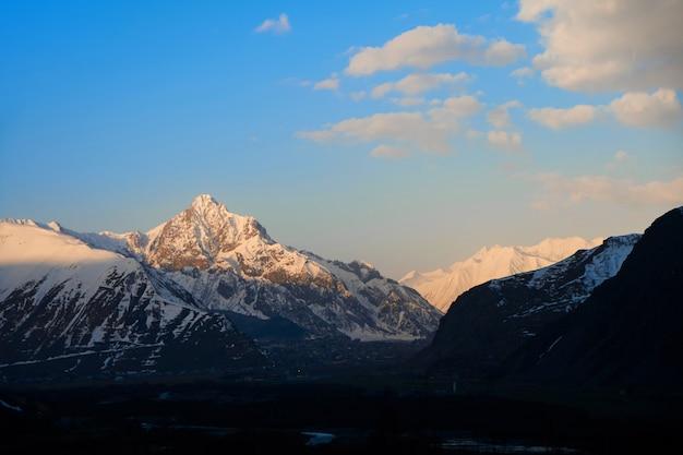 Świt w górach. promienie słoneczne padają na szczyt góry. póki w dolinie jest jeszcze ciemno. inspirujący poranek dla podróżnika.