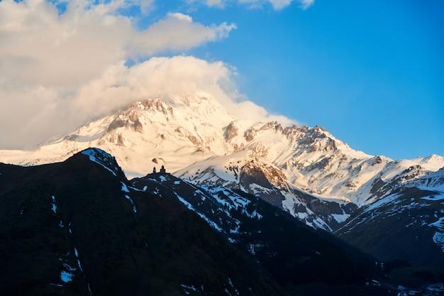 Świt w górach. promienie słoneczne padają na szczyt kazbeku. inspirujący poranek dla podróżnika.