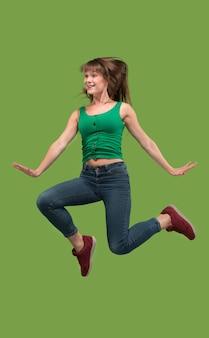 Swoboda poruszania się. ujęcie w powietrzu całkiem szczęśliwej młodej kobiety skaczącej i wskazującej na pomarańczowym tle studia. uciekająca dziewczyna w ruchu lub ruchu.