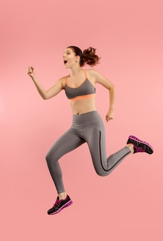 Swoboda poruszania się. ujęcie w powietrzu całkiem szczęśliwej młodej kobiety skaczącej i wskazującej na pomarańczowym tle studia. uciekająca dziewczyna w ruchu lub ruchu