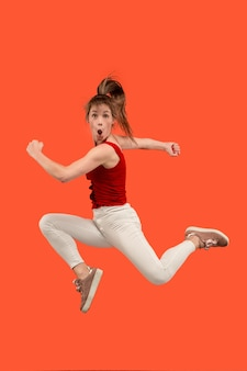 Swoboda poruszania się. ujęcie w powietrzu całkiem szczęśliwej młodej kobiety skaczącej i wskazującej na pomarańczowym tle studia.