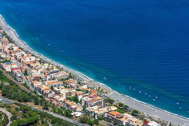 Sycylia. widok linii wybrzeża morza jońskiego z góry na santa teresa di riva w słoneczny letni dzień. niebieskie morze,