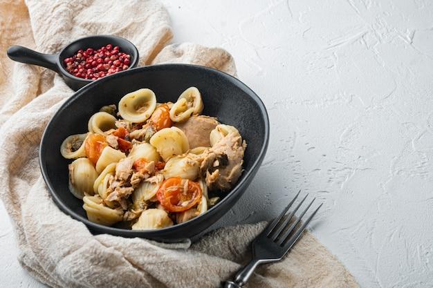 Sycylijski makaron z tuńczykiem w misce, na białym tle z miejscem na tekst