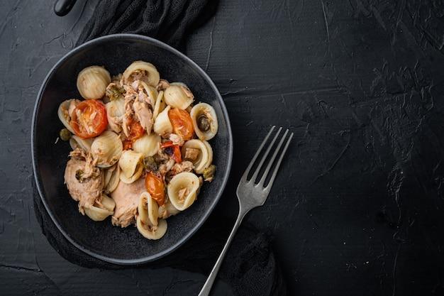 Sycylijski makaron z tuńczykiem w misce, na czarnym tle, widok z góry z miejscem na tekst
