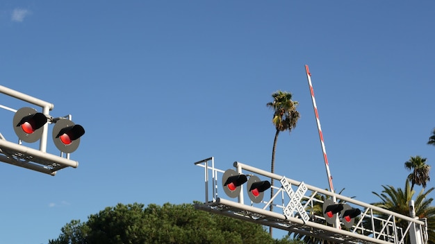 Sygnał ostrzegawczy na przejazdach kolejowych w usa. uwaga crossbuck i czerwone światło na skrzyżowaniu dróg kolejowych w kalifornii.