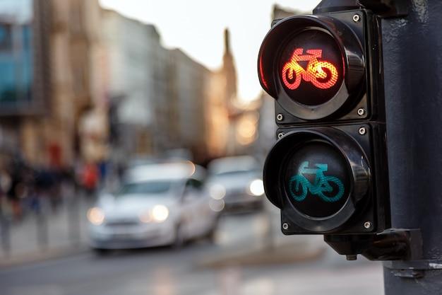 Sygnalizacja świetlna dla rowerów zapala się na czerwono na tle poruszających się samochodów wieczorem na ulicy miasta