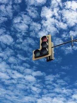 Sygnalizacja świetlna na tle błękitnego nieba i mnóstwo białych chmur