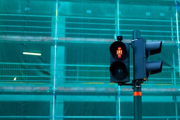 Sygnalizacja świetlna przejścia dla pieszych z czerwonym mężczyzną zakazującym przejścia.