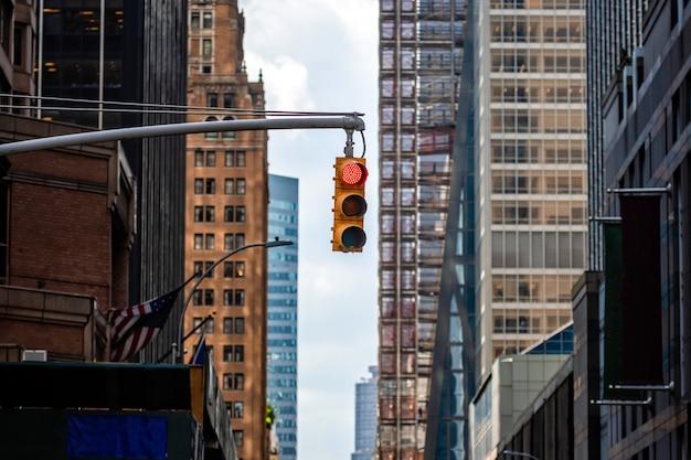 Sygnalizacja świetlna z czerwonym światłem nad ulicą manhatan wśród wielu drapaczy chmur
