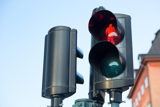 Sygnalizacja świetlna z czerwonym światłem zapalona dla pieszych na tle nieba w sztokholmie w szwecji