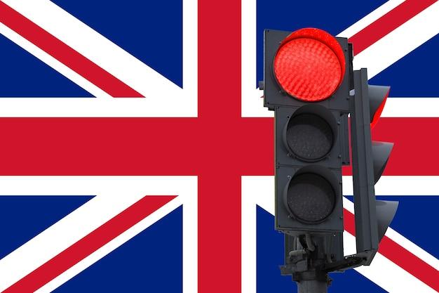 Sygnalizacja świetlna z palącym się sygnałem zakazu. na tle flagi wielkiej brytanii. zakaz wjazdu