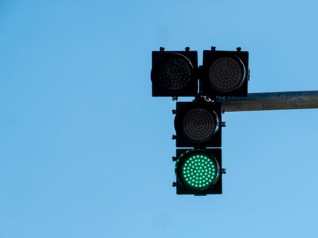 Sygnalizacja świetlna z włączonym zielonym światłem, z niebieskim niebem.