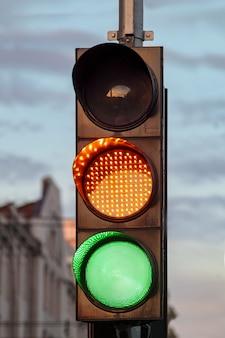 Sygnalizacja świetlna. zielony sygnał drogowy. żółte światło drogowe na jezdni w tle chmur. kolorowy znak idź lub ostrzegawczy