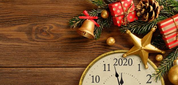 Sylwester 2020. zegar w stylu retro z ozdób choinkowych i prezentów na brązowym tle drewnianych. ostatnie chwile przed bożym narodzeniem lub nowym rokiem