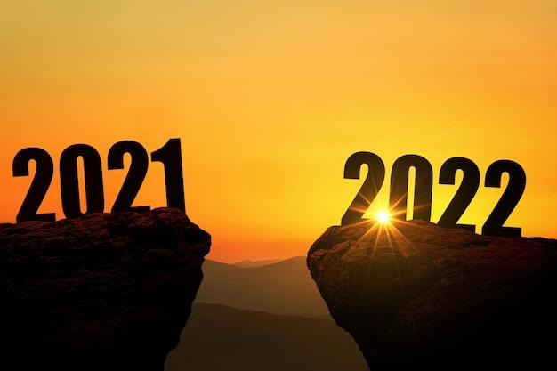Sylwester 2022 na górze o zachodzie słońca, koncepcja. 2021 i 2022 na klifie o wschodzie słońca, kreatywny pomysł. wolna przestrzeń na projekt