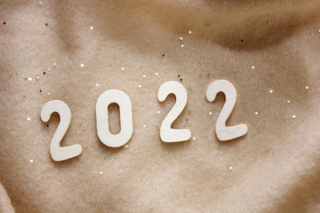 Sylwester 2022. numer sylwestrowy wyłożony jest drewnianymi cyframi na beżowym kocyku z polaru obsypanego złotymi cekinami. szczęśliwego nowego roku