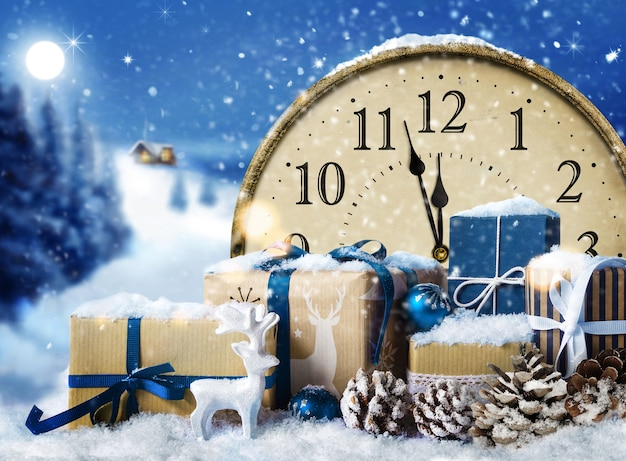 Sylwester. zegar w stylu retro z pudełka na prezenty świąteczne i dekoracje pokryte śniegiem na tle niebieskiego krajobrazu noc.