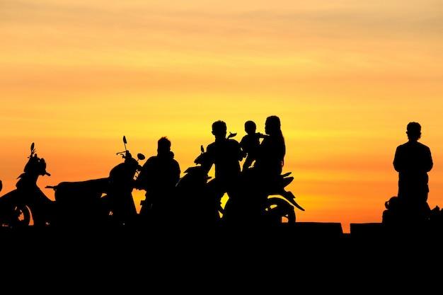 Sylwetek ludzie i rodzina na motocyklu przy zmierzchem, sylwetki fotografia