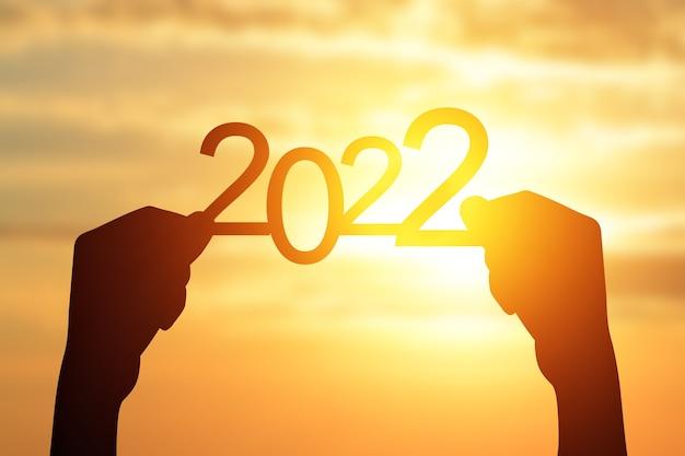 Sylwetka 2022 w dłoni wschód słońca w tle