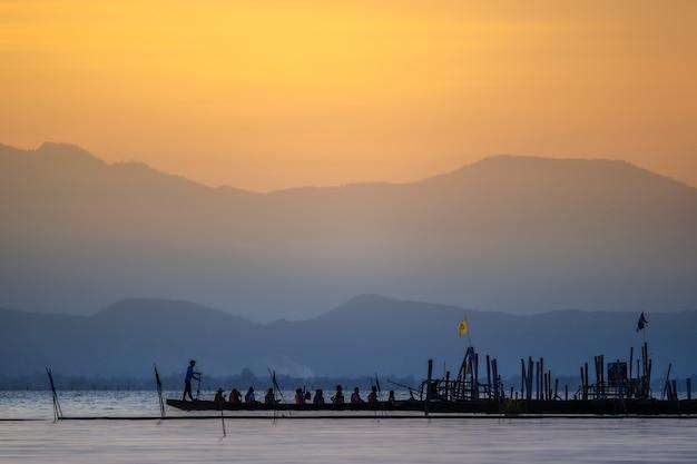 Sylwetka azjatyccy turyści relaksuje na drewnianej łodzi.