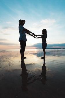 Sylwetka azjatyckich matki i córki, trzymając rękę i grając na plaży razem w czasie zachodu słońca z pięknym morzem i niebem. rodzina cieszy się koncepcją natury.