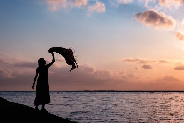 Sylwetka azjatyckiej kobiety relaksuje się z podniesionym materiałem na tropikalnym morzu z kolorowym niebem