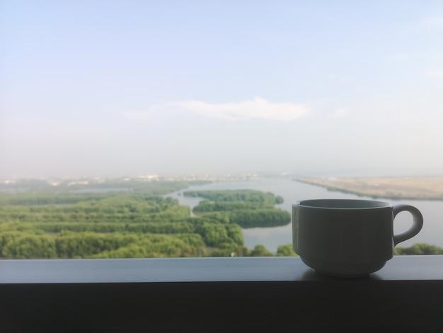 Sylwetka biała szklana filiżanka na balkonie z lasem nieba i jeziorem w tle