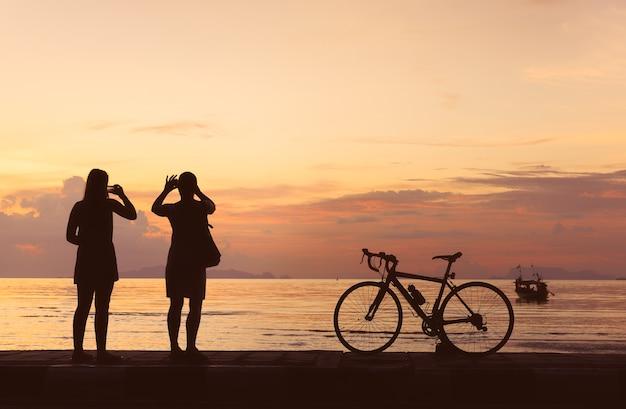 Sylwetka bicykl i ludzie biorą fotografię przy plażowym zmierzchu tłem