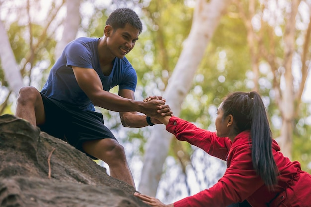 Sylwetka biegacza szlakowego z ręką pomagającą sobie nawzajem wspinać się na szczyt góry