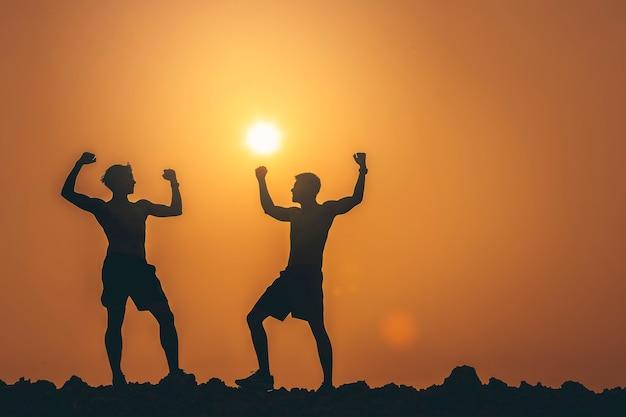 Sylwetka biegaczy stojących i z otwartymi ramionami ze zdrowymi na szczycie góry