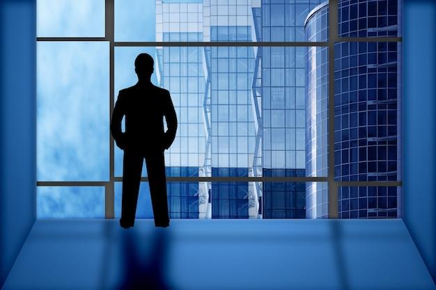 Sylwetka biznesmena wygląda na okno biurowe na budynkach biznesowych, błękitne niebo i chmury
