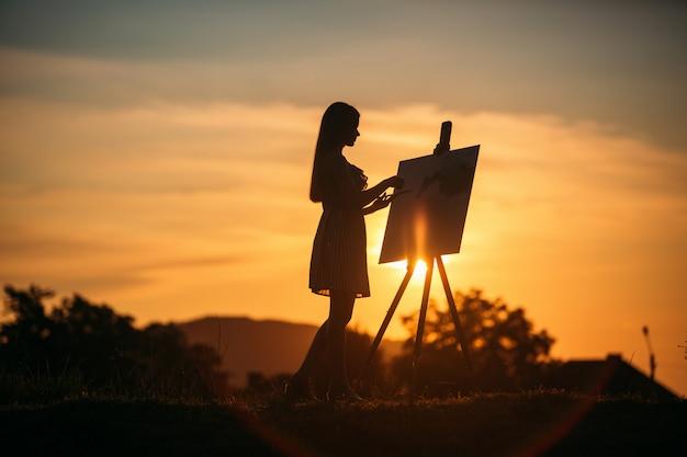 Sylwetka blondynki maluje obraz na płótnie. paleta z farbami i szpachelką, letni słoneczny dzień