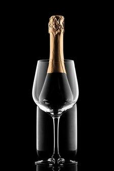 Sylwetka butelki szampana i szkło izolowane na czarnym tle