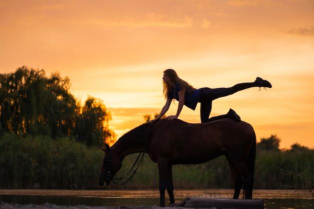 Sylwetką była szczupła dziewczyna ćwicząca jogę na koniu, o zachodzie słońca koń stoi w jeziorze, c.