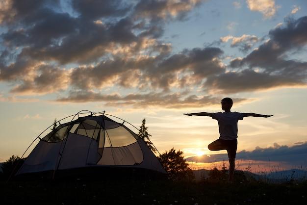 Sylwetka chłopca w praktyce jogi na szczycie góry o świcie w pobliżu kempingu pod niebem z chmurami i jasne poranne słońce. zapierający dech w piersiach krajobraz gór i wzgórz, nad którymi wschodzi słońce