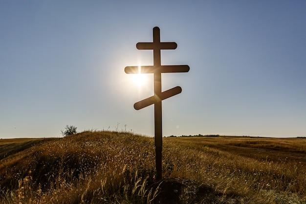 Sylwetka chrześcijańskiego krzyża prawosławnego na zachód słońca.